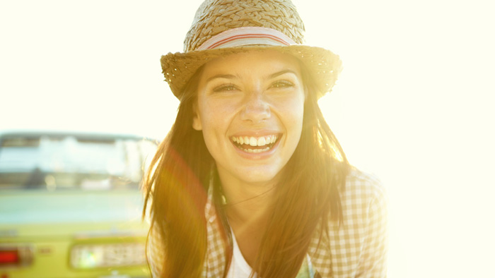 Woman smiling outside on a sunny day in front of a car