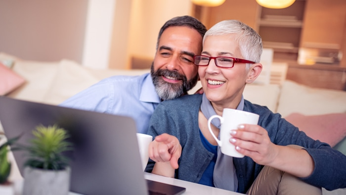 Older couple sits next to each other looking at laptop